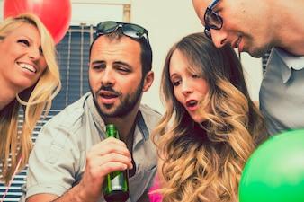 Vrienden zingen met een fles bier
