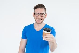 Vrolijke energetische jonge man met uitgaand koffie