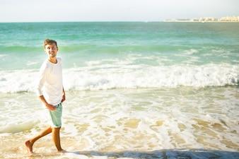 Vrolijke jonge man kijkt omhoog in de lucht die in schuimende golven loopt