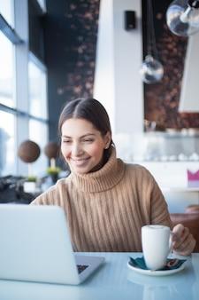 Vrolijke vrouw met behulp van laptop in coworking ruimte