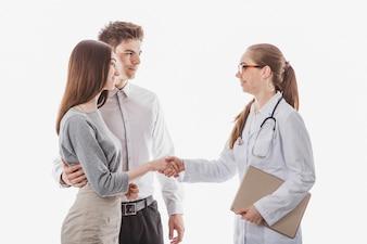 Vrouw arts schudden handen met paar