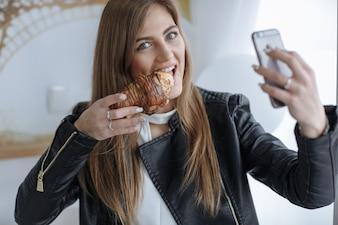 Vrouw die een foto met haar mobiele telefoon tijdens het eten van een croissant