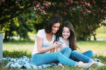 Vrouw en meisje in park met smartphone