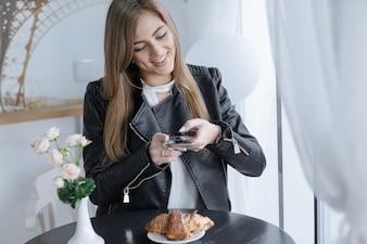 Vrouw fotograferen met haar mobiele telefoon een chocolade croissant
