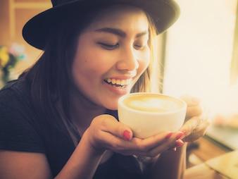 Vrouw glimlachend met een kopje koffie