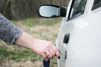Vrouw hand opening auto deur met sleutel