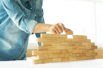 Vrouw in jeans shirt houden blokken hout spel (jenga) Bouwen een kleine bakstenen muur Risico concept