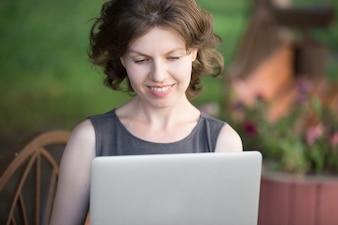 Vrouw lachend tijdens het typen op laptop