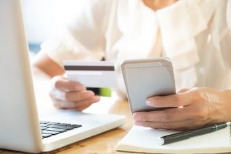 Vrouw met mobiele telefoon en creditcard op laptop voor online winkelen