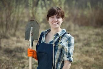 Vrouw met spade en spruit in het voorjaar