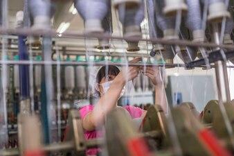 Vrouwwerkers in maskers en hoeden werken in textielfabrieken