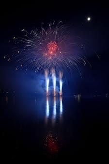 Vuurwerk. Mooi kleurrijk vuurwerk op het wateroppervlak met een schone zwarte achtergrond. Leuk festival en wedstrijd van Brandweer Brno Dam - Tsjechië.