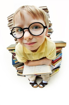 Weinig jongen met een bril, omringd door boeken