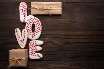 """Word """"love"""" met bruine giften op een houten tafel"""