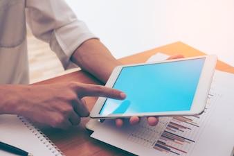Zakenman handen op een tafel met tablet in een kantoor