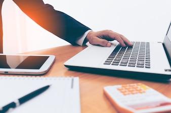 Zakenman handen op laptop met tablet, telefoon en kopje koffie in een kantoor