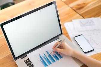 Zakenvrouw hand met Financial charts en mobiele telefoon over laptop op de tafel.