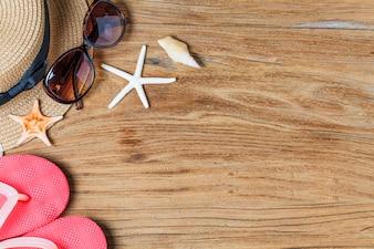 Zand en schelpen op de houten vloer van het zomerconcept