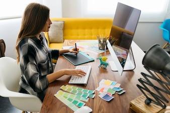 Zijaanzicht van grafische ontwerper die bij bureau werkt