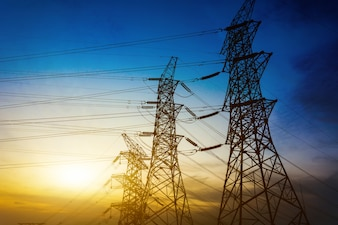 Zon instelling achter het silhouet van elektriciteitspylonen