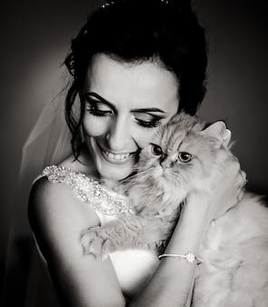 Zwart-wit foto van gelukkige bruid die pluizige kat achter haar gezicht houdt