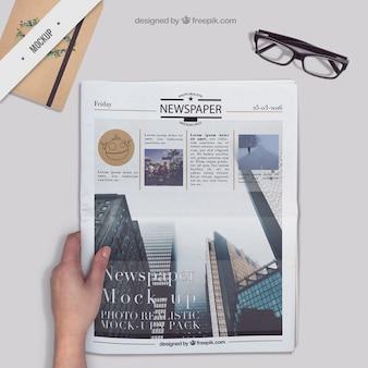 Krant op een desktop met een agenda en een bril