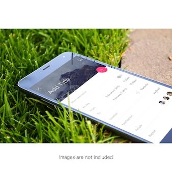 Mobiele telefoon op gras mock up