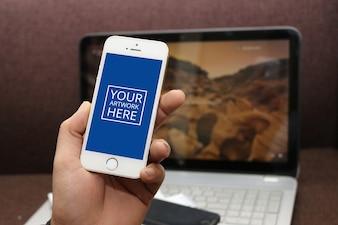Smartphone met groen scherm in de hand met laptop achtergrond