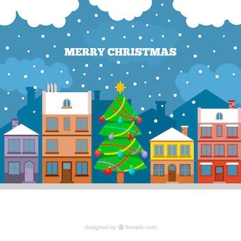 Achtergrond van huizen en kerstboom in plat ontwerp
