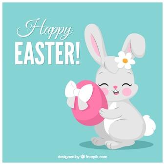 Blauwe achtergrond van Pasen met konijn knuffelen een ei