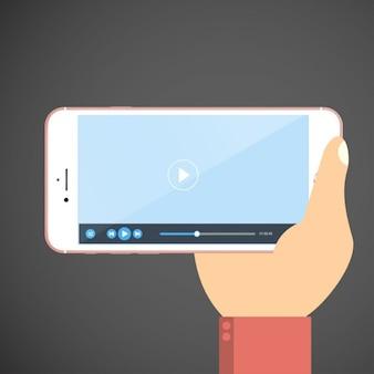 De hand houdt smartphone met videospeler app op het scherm