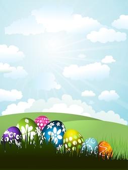 Kleurrijke Paaseieren in het gras op een zonnige landschap achtergrond