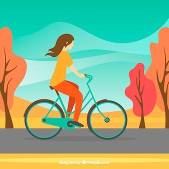 Vrouw rijden fiets en herfst landschap