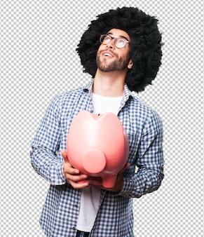 Afro młody człowiek trzyma skarbonkę
