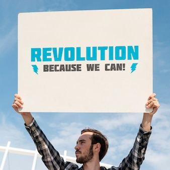 Aktywista trzyma makietę tablicy
