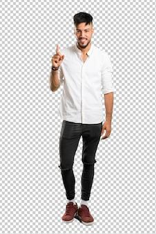 Arabski młody człowiek z białą koszulę licząc numer jeden znak