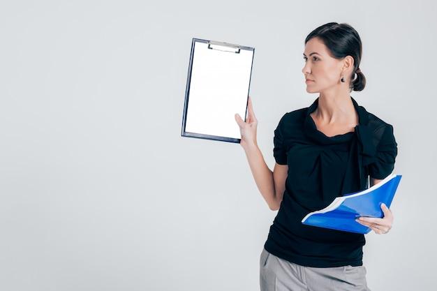 Atrakcyjna biznesowa kobieta trzyma falcówkę z dokumentami