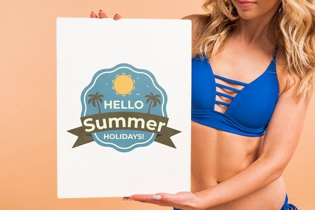 Atrakcyjna kobieta przedstawia okładkowego mockup w bikini