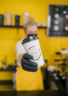 Barista w połowie strzału trzymając makietę filiżanki kawy