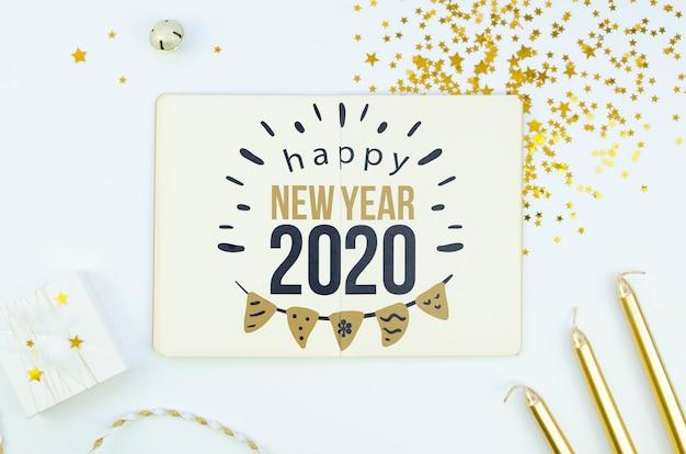 Biała kartka z cytatem szczęśliwego nowego roku 2020 i złotymi akcesoriami