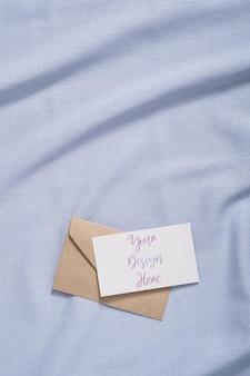 Biała pusta karta papieru i makieta koperty na niebieskim neutralnym kolorze tkaniny