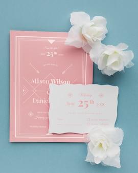 Białe kwiaty z zaproszeniem na ślub