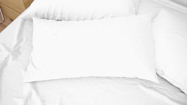 Białe poduszki na łóżkowym zbliżeniu