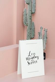 Biały plakat na pastelowo różowej podłodze autorstwa kaktusów