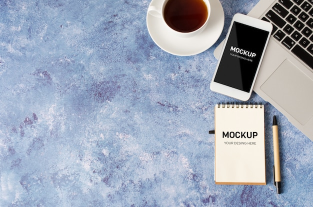 Biały smartfon z czarnym pustym ekranem na biurku z laptopem, pustym notatnikiem i filiżanką herbaty. makieta telefonu.