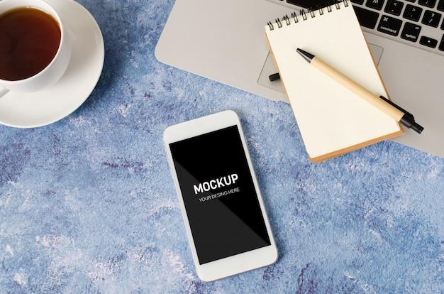 Biały smartfon z czarnym pustym ekranem na biurku z laptopem, pustym notatnikiem i filiżanką herbaty