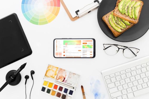 Biurko w widoku z góry z tostem z awokado i makietą telefonu