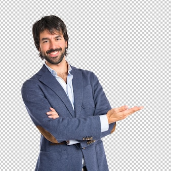 Biznesmen przedstawia coś nad odosobnionym białym tłem