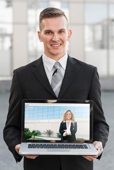 Biznesmen przedstawia laptopa makieta