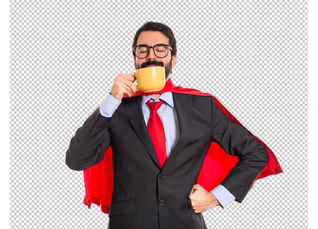Biznesmen ubrany jak superbohater picia kawy